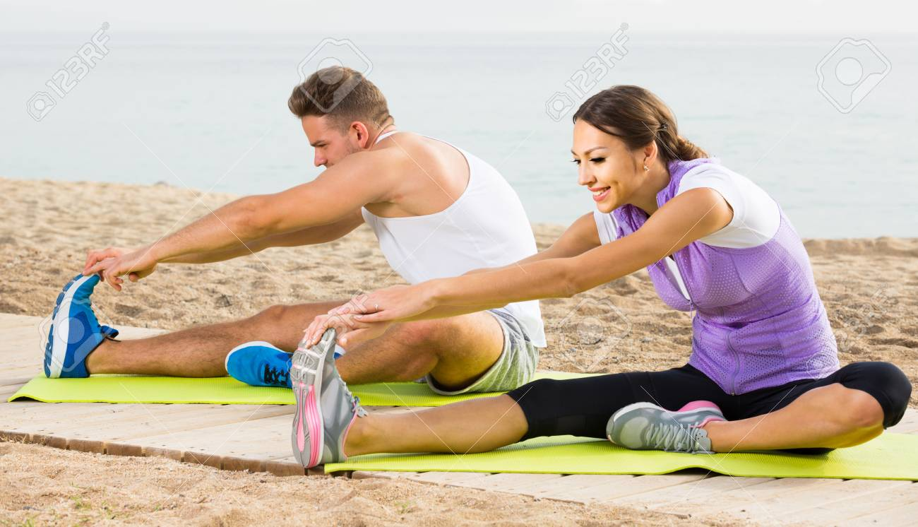 Happy Spanish Guy And Girl Practising Yoga Poses Sitting On Beach Stock Photo Picture And Royalty Free Image Image 88556800