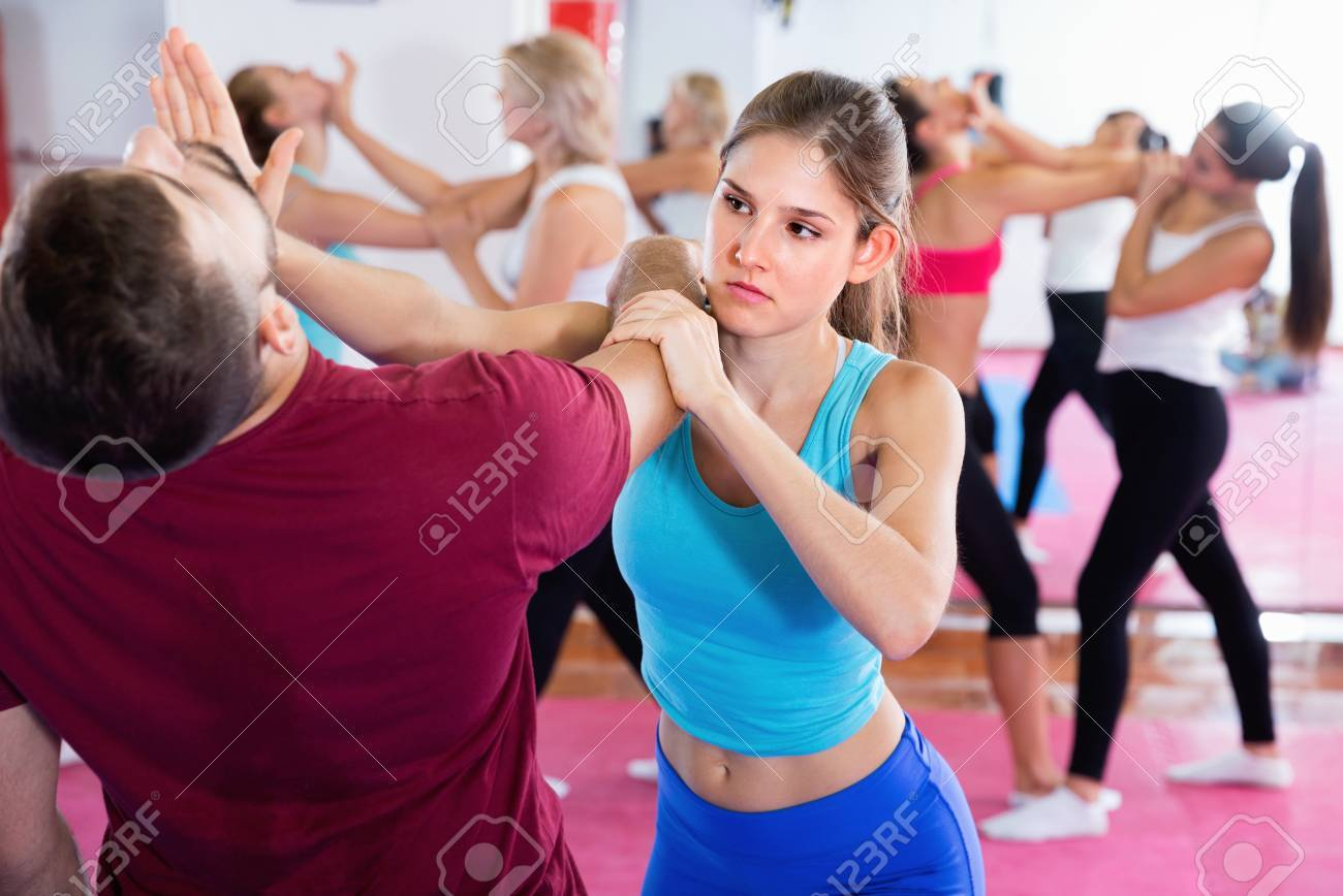 Glad cheerful positive smiling female is training self-defence