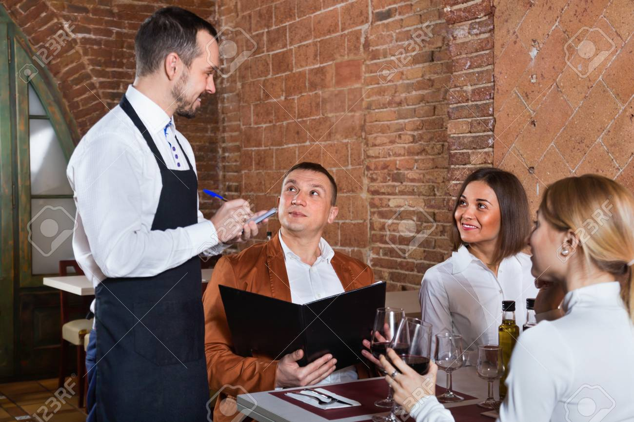 Male waiter taking order from visitors in country restaurant - 90459241