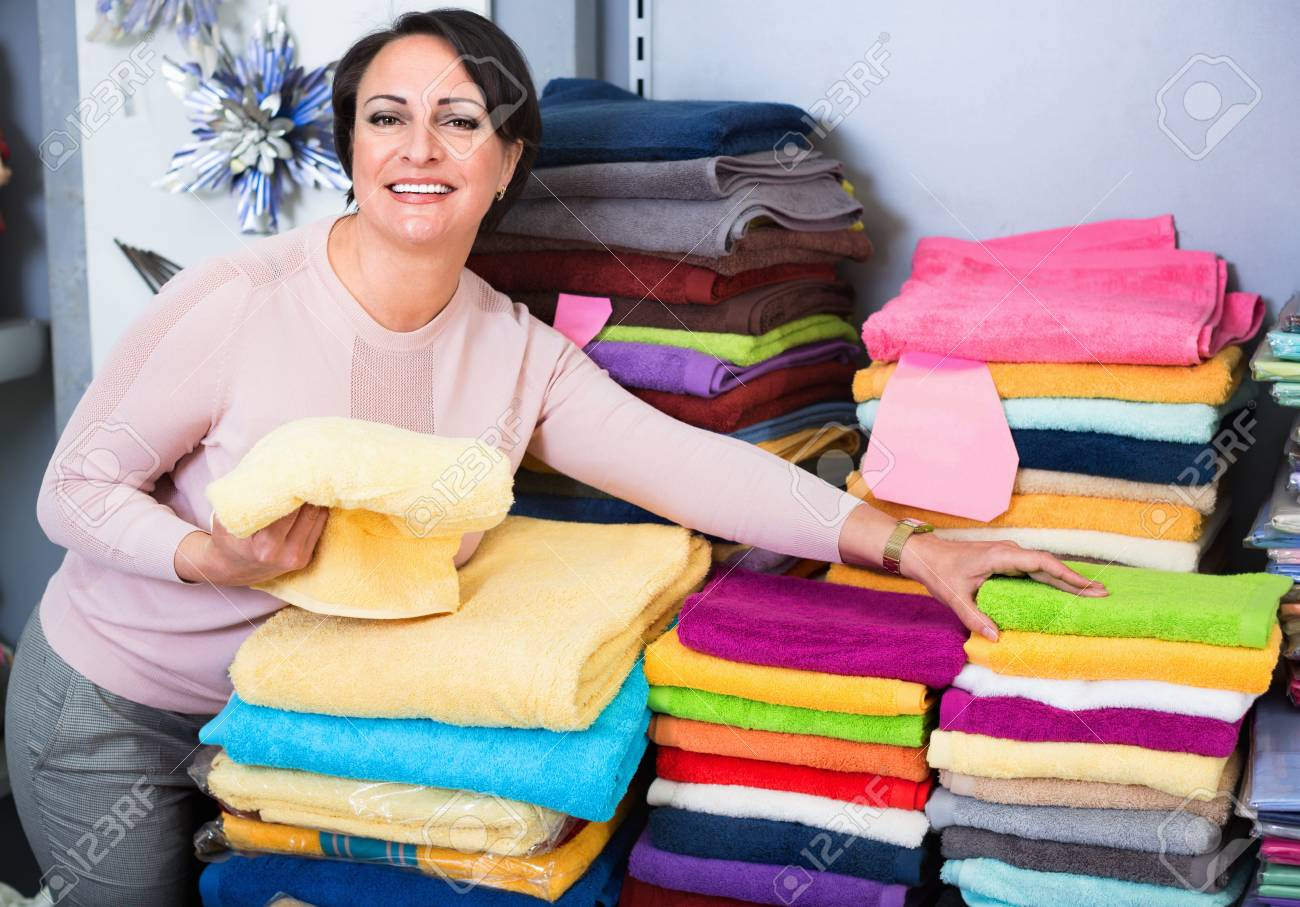 Smiling Female Customer Posing With Loop Towel And Bed Sheets Inside  Textile Store Stock Photo