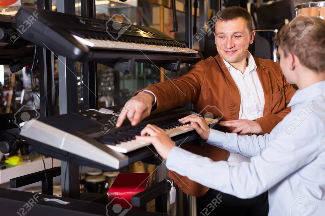 Smiling salesman demonstrates a synthesizer to a boy in a music