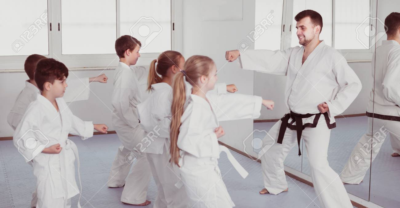 Smiling children doing karate kicks with male coach during karate
