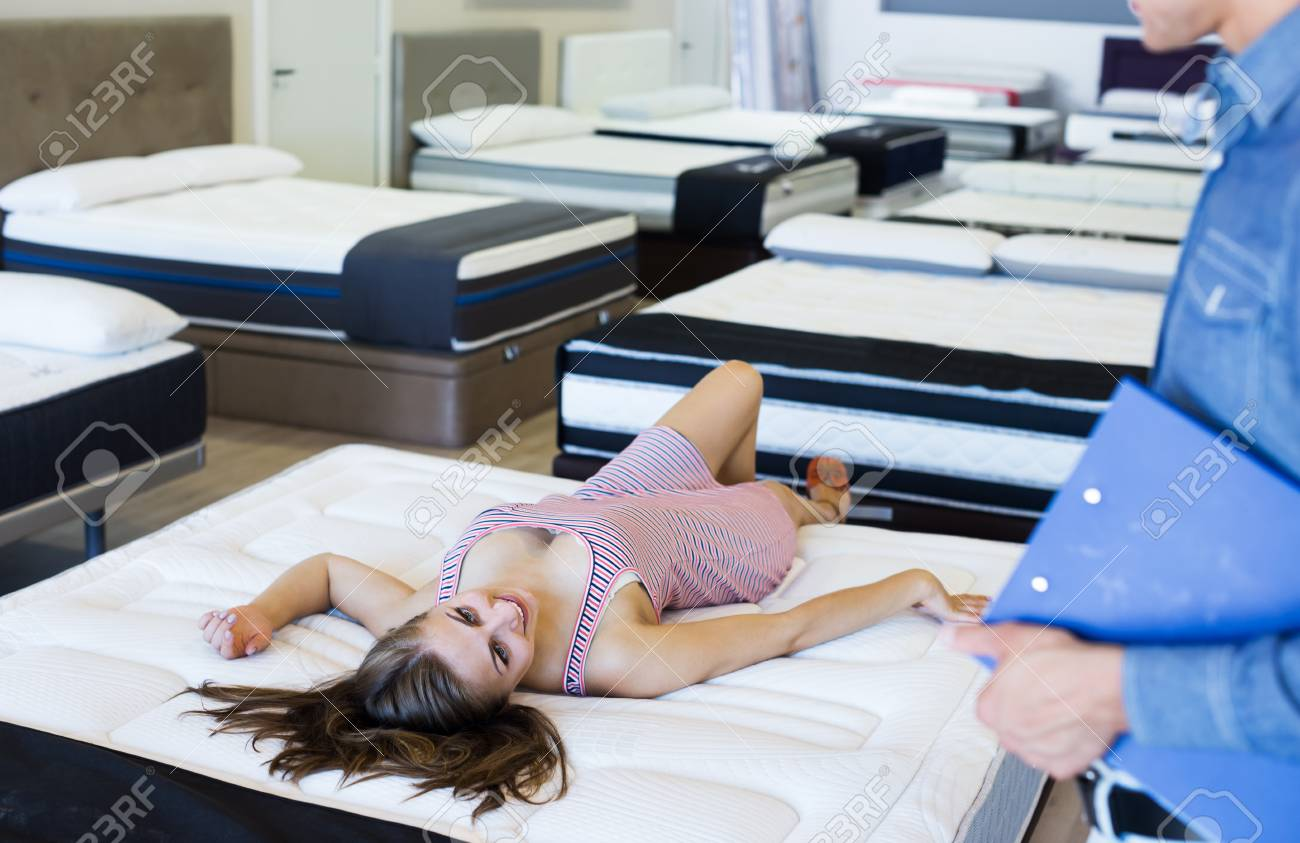 Stock Photo   Successful Seller Offering Mattress To Buyer In Furniture  Salon