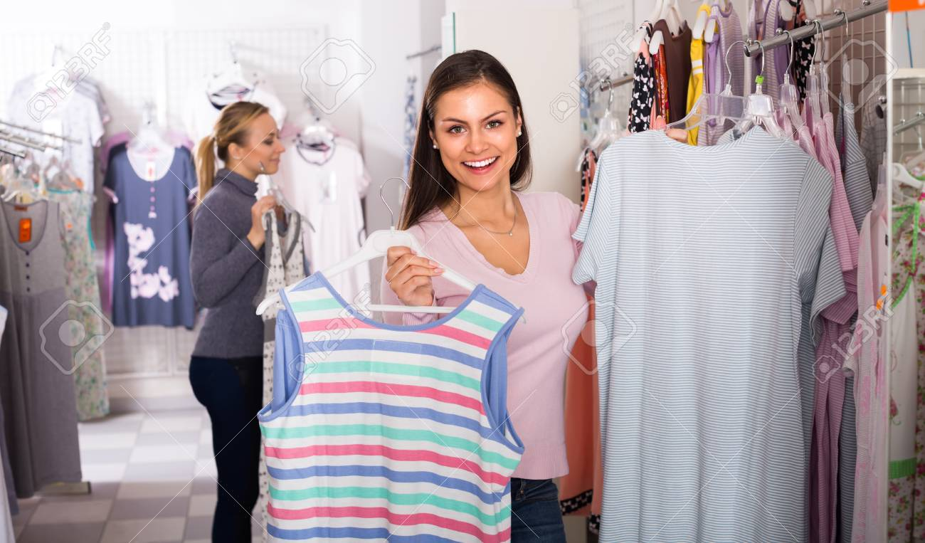 00b9cac8ed6f Stock Photo - Two cheerful young women shopping comfortable sleepwear  together in lingerie department