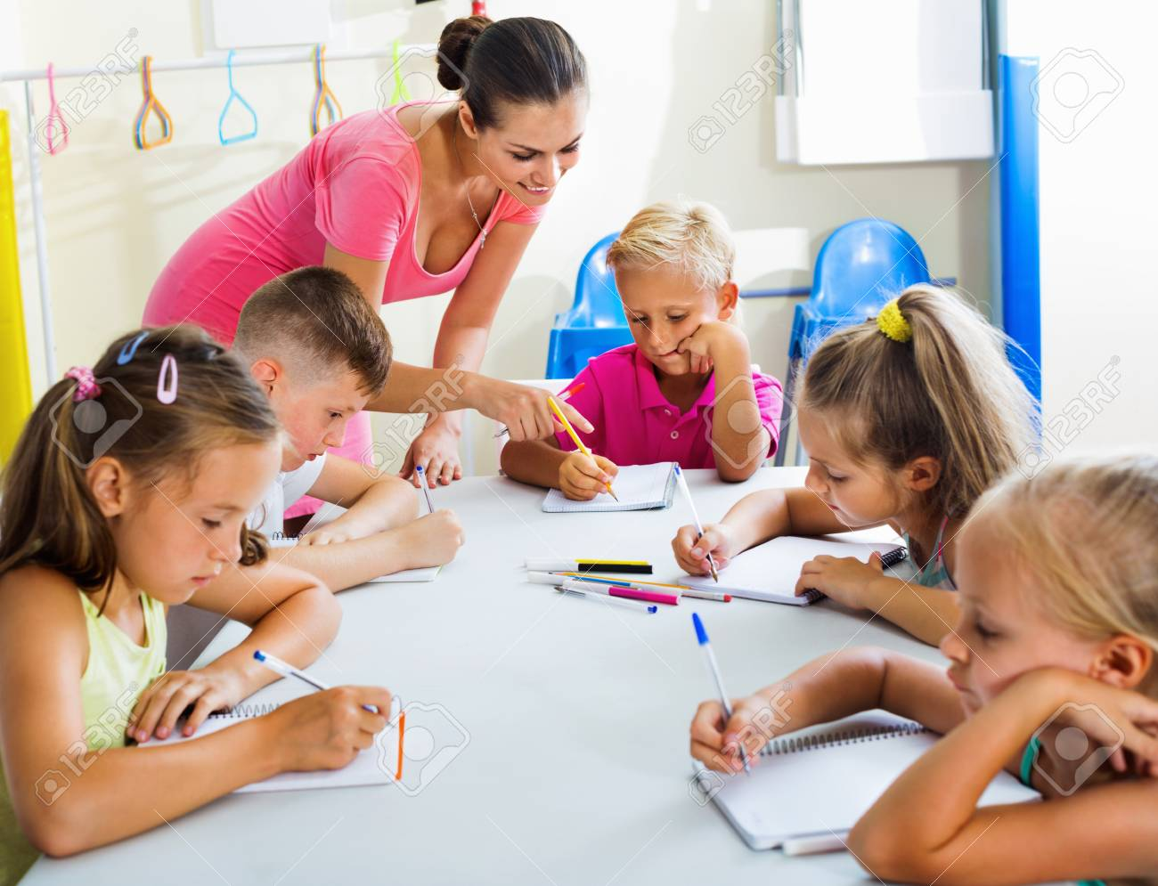 happy positive kids writing together with tutor at school class
