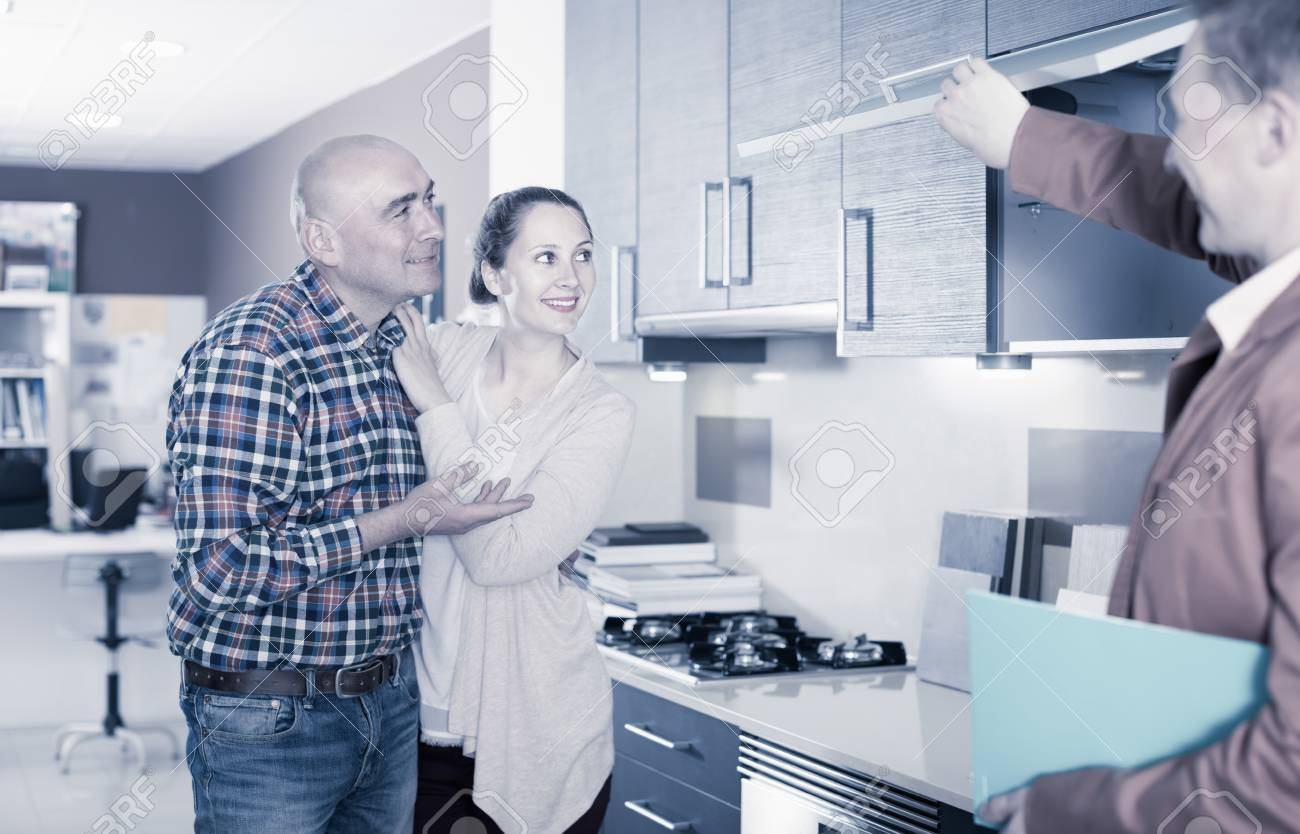 Young couple examines kitchen cabinets in a furniture store
