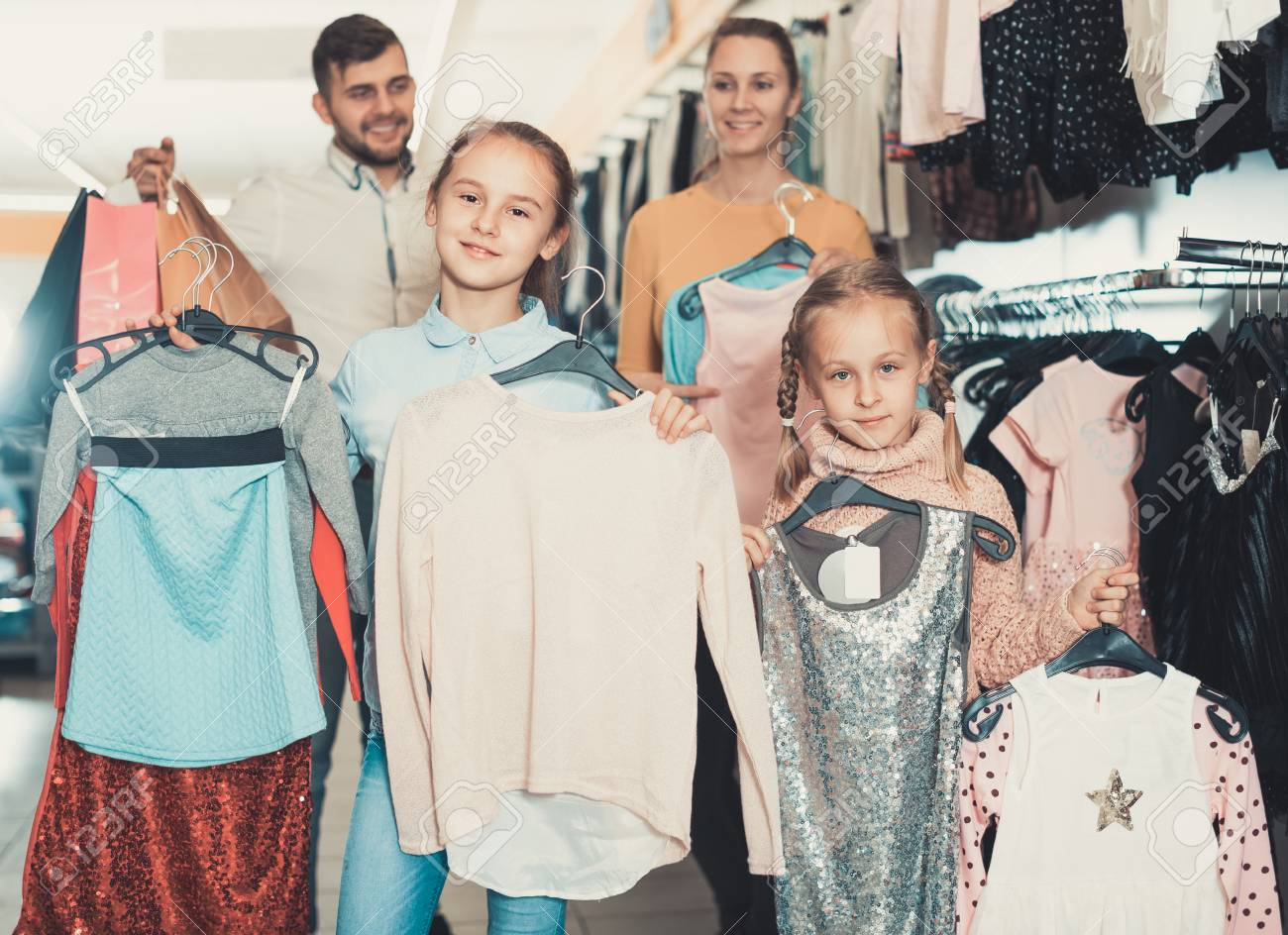 9f90e39d4 Two smiling little sisters with mum and dad during family shopping in clothes  store Stock Photo