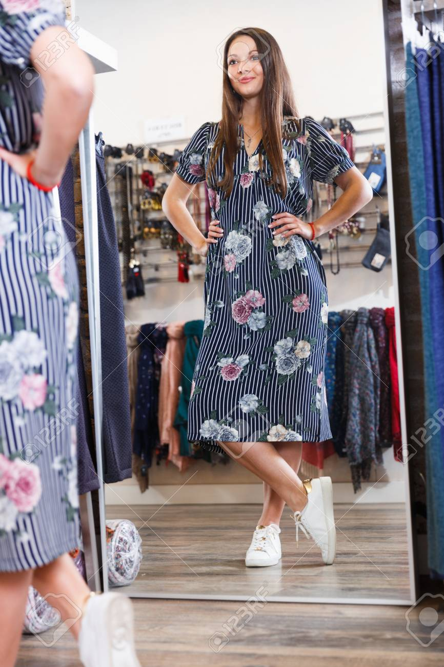 f9848b0460c Positive cute girl customer posing in new fashion dress at mirror in the  shop Stock Photo