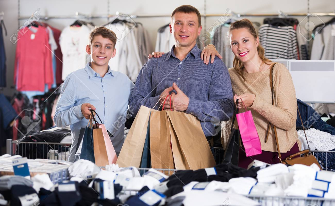 a7f604c0bc Family couple with teen displaying shopping bags with purchases in clothes  shop Stock Photo - 96749165