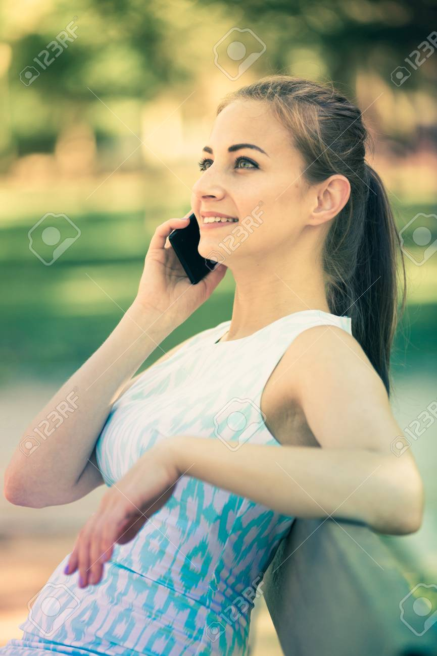 smiling swiss girl sitting on a bench and using telephone in stock