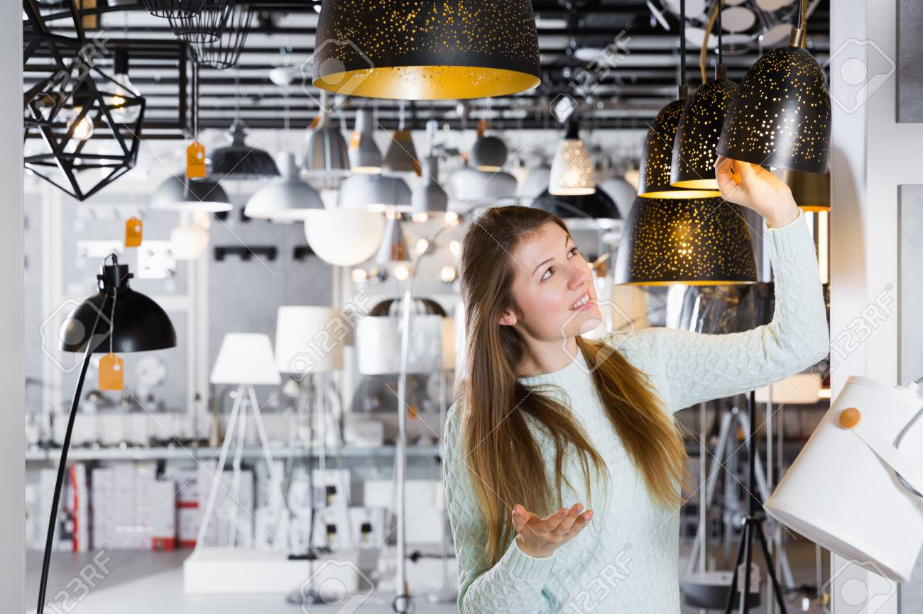Positive girl buying plummed lamp in the modern furniture store stock photo 97580803