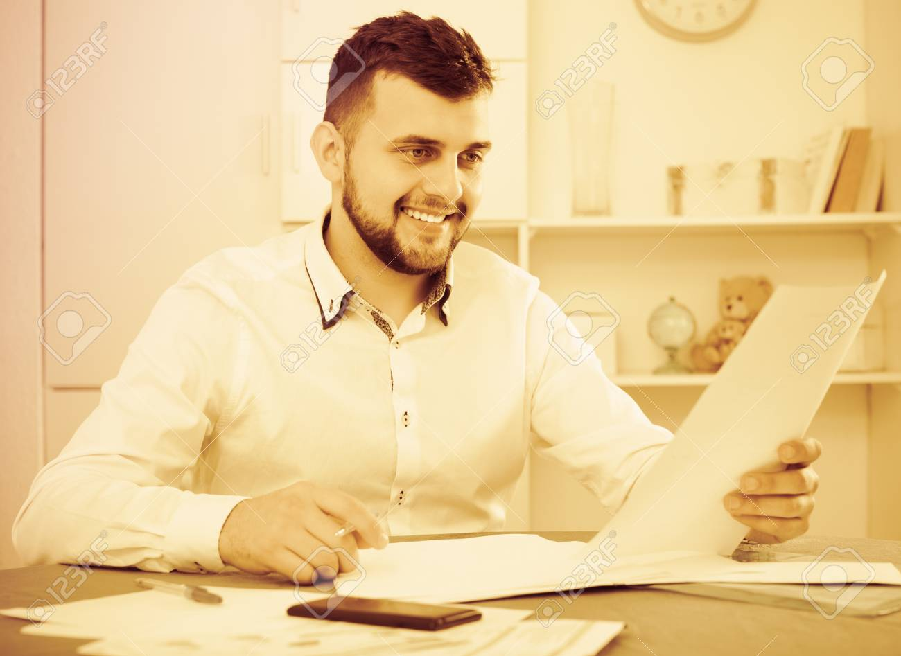 smiling male preparing agreement papers about finances at home stock
