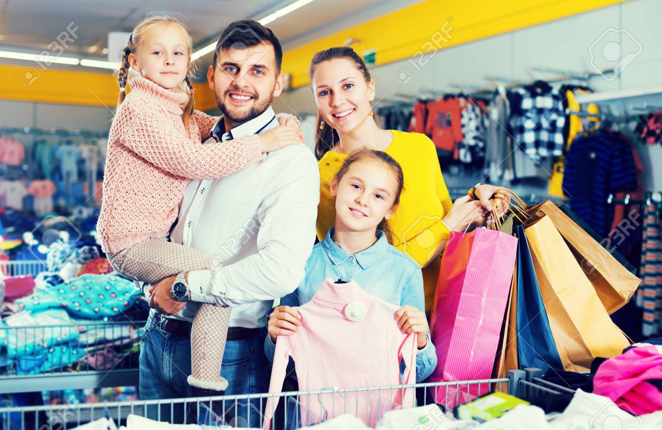 a2411f4f3 Young cheerful family with two daughters after shopping in clothes store  Stock Photo - 97754036