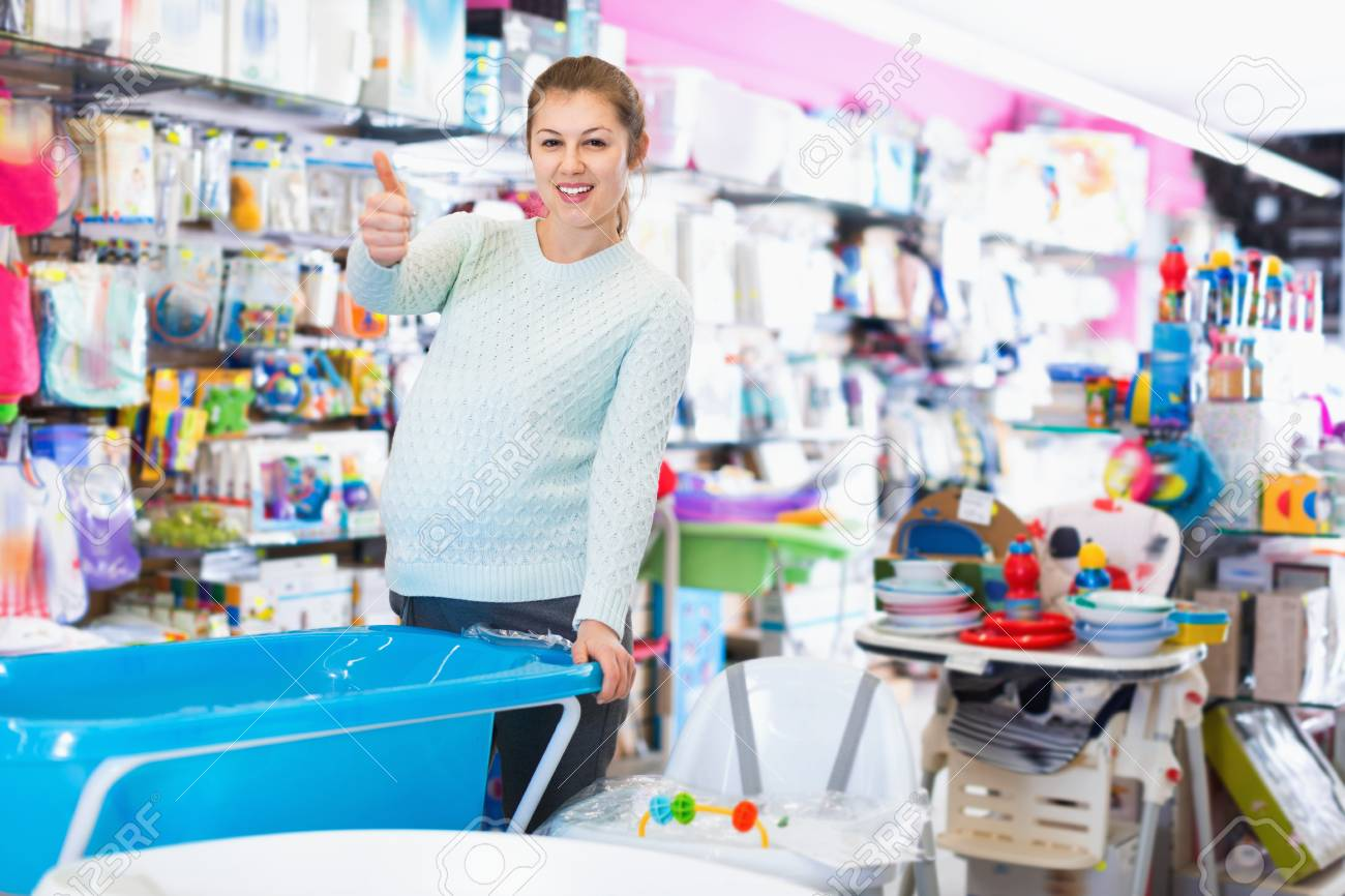 Cheerful Positive Pregnant Woman Is Choosing Baby Bath In The ...