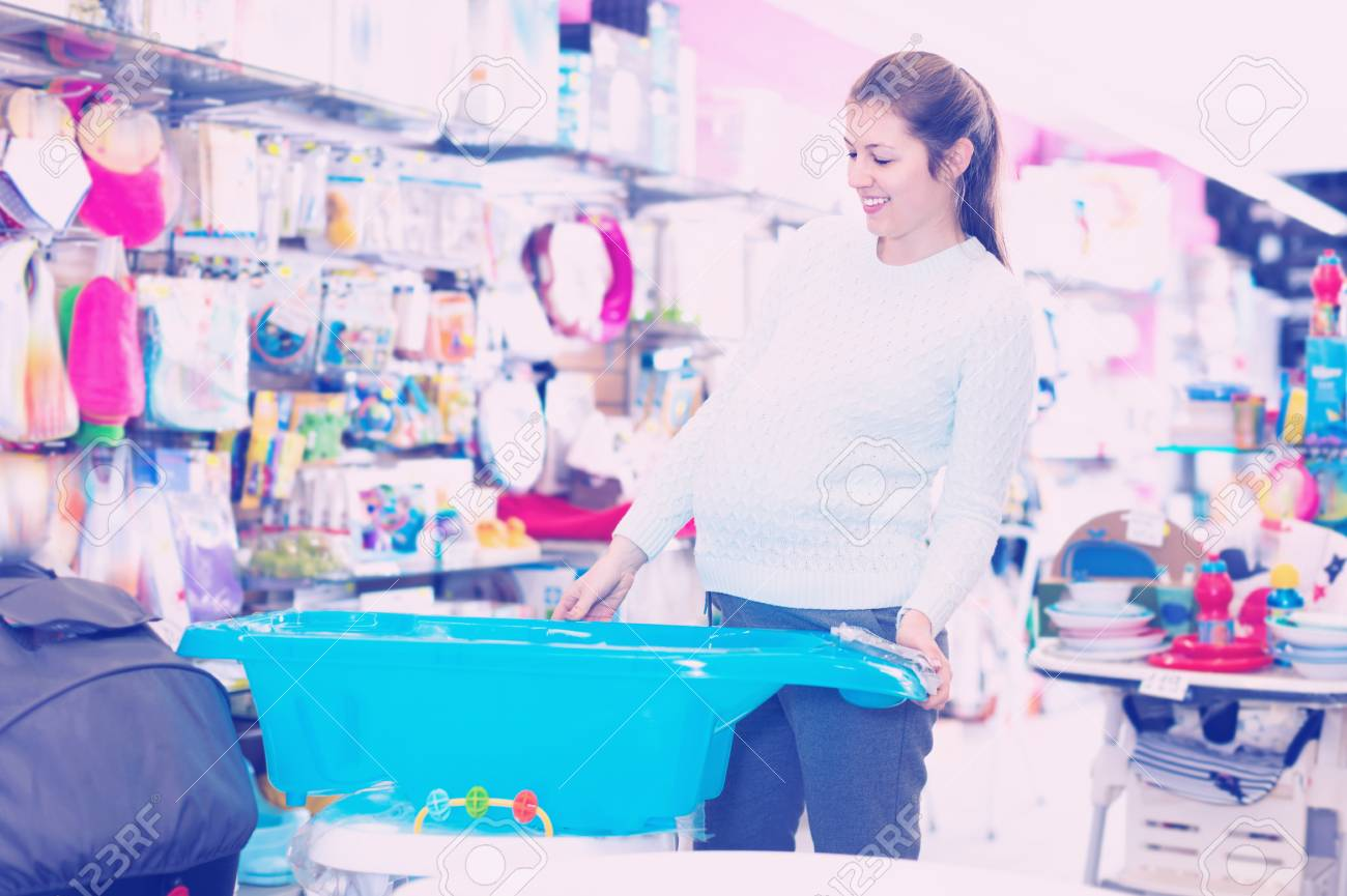 Happy Positive Pregnant Woman Is Choosing Baby Bath In The.. Stock ...