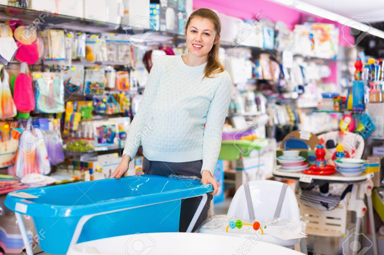 Cheerful Smiling Pregnant Woman Is Choosing Baby Bath In The.. Stock ...