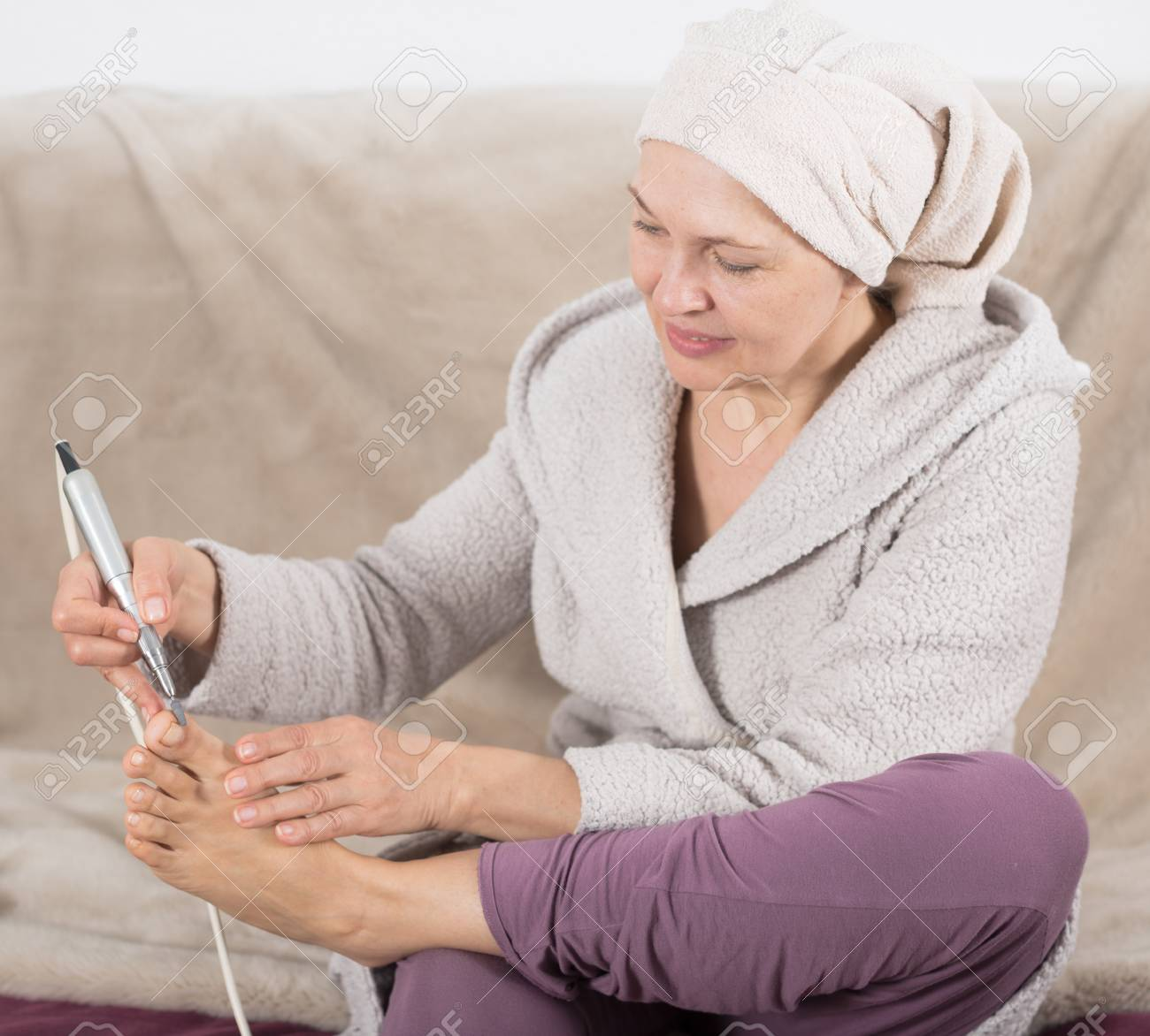 Elderly woman performing pedicure with special devices at home