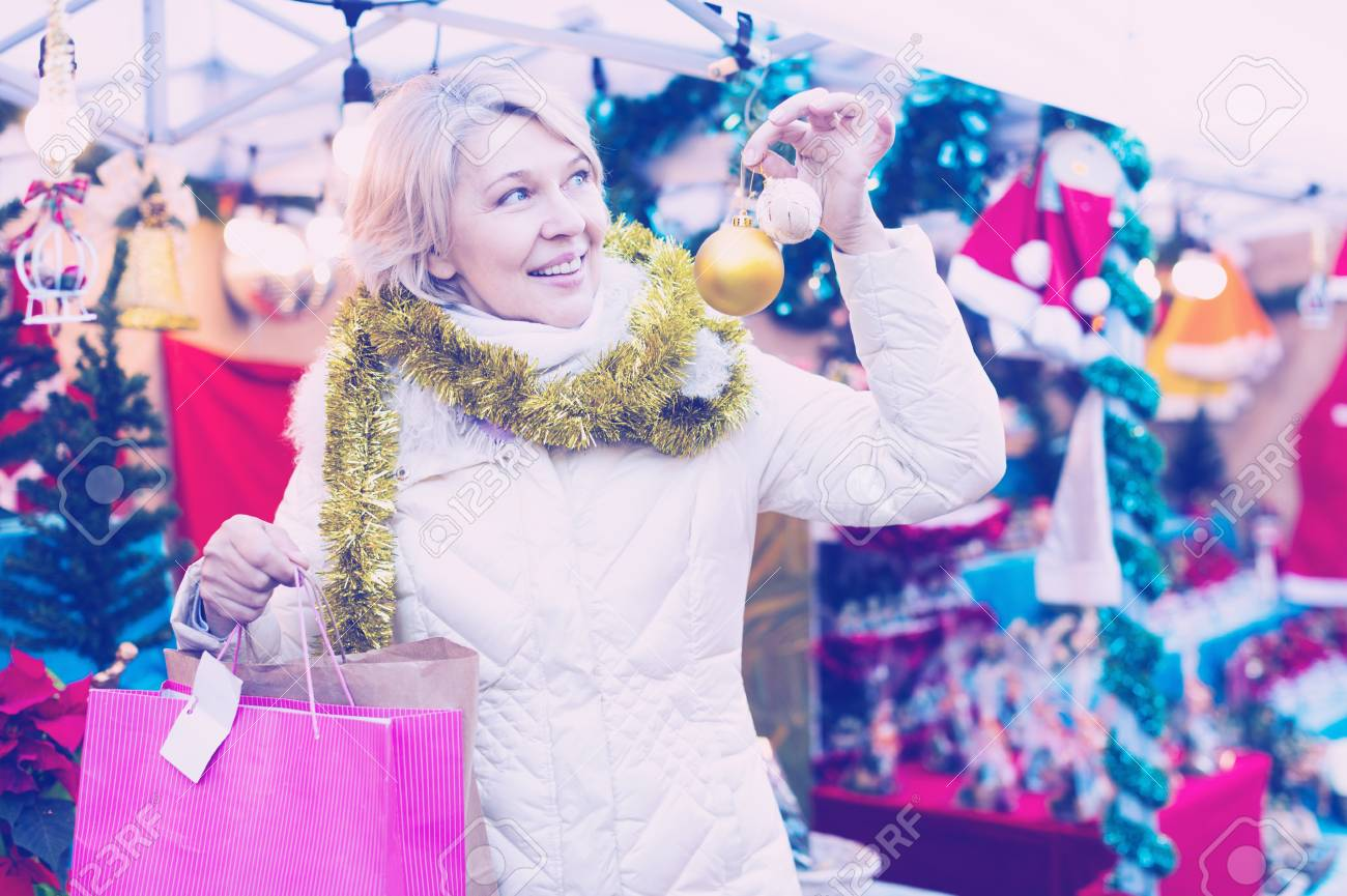Portrait of happy mature woman in tinsel with Christmas toys at fair  outdoor Stock Photo -