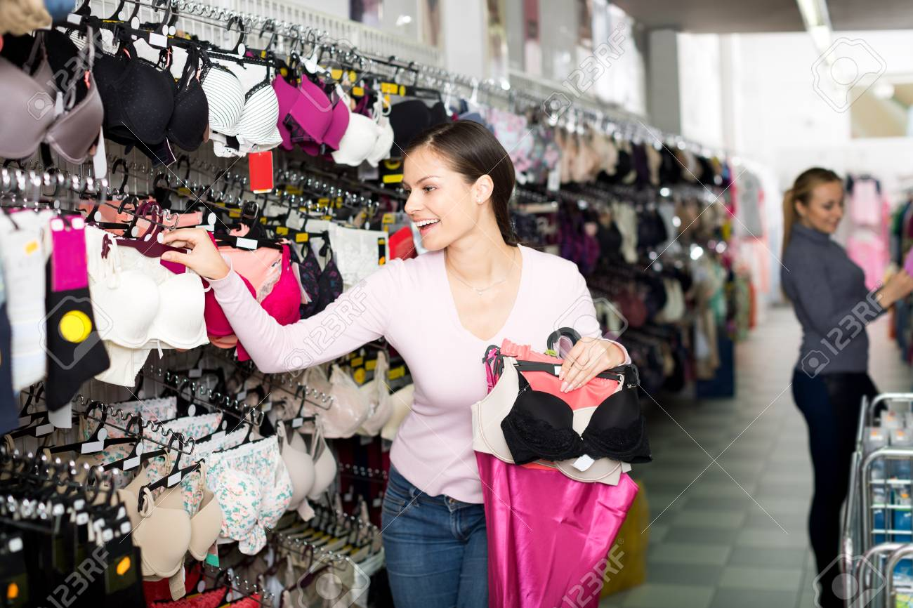 0e169345c Happy young woman choosing sexy silky bra in lingerie shop Stock Photo -  98669253