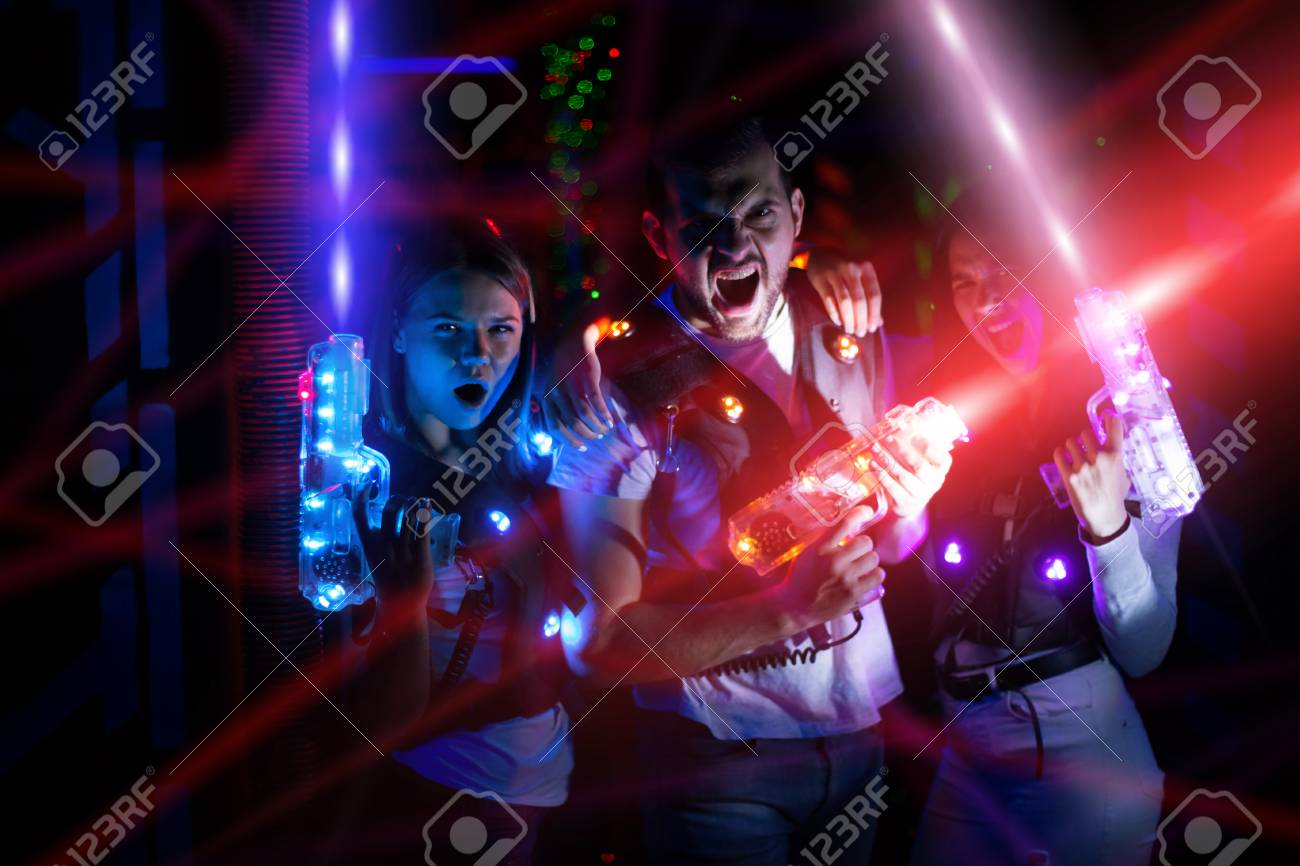 Group portrait of young people in colorful beams of laser guns having fun on lasertag arena - 101617574