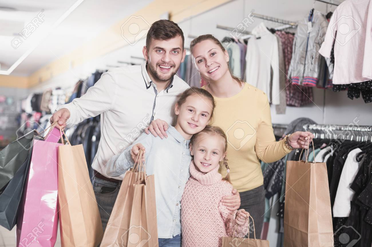 Young Glad Parents With Two Little Girls During Family Shopping