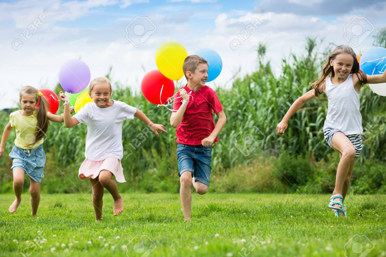 Active Kids Having Fun And Running With Multicolored Balloons At Backyard In Summer Time Stock P O