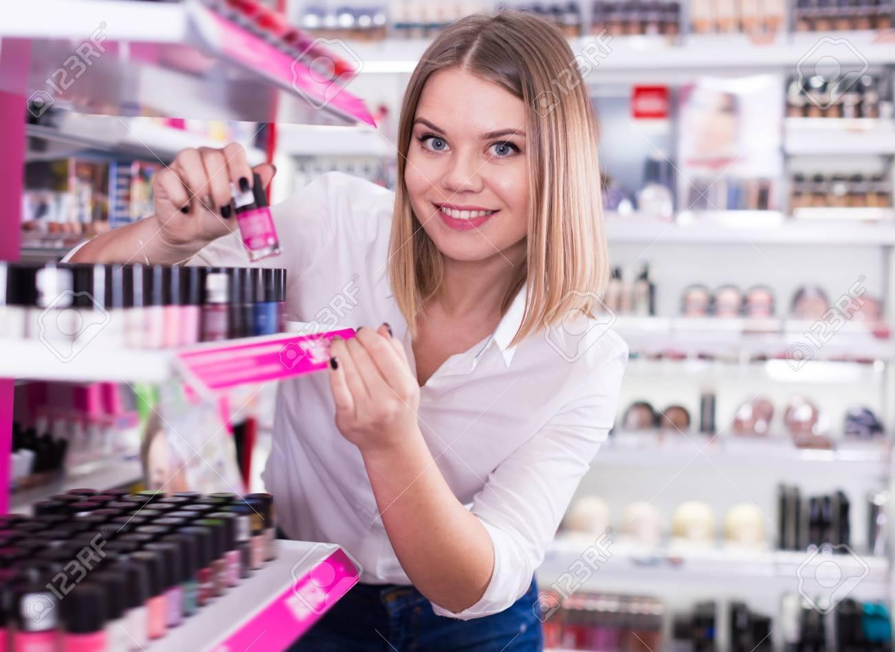 Happy Girl Choosing Color Of Nail Polish At Cosmetics Store Stock ...