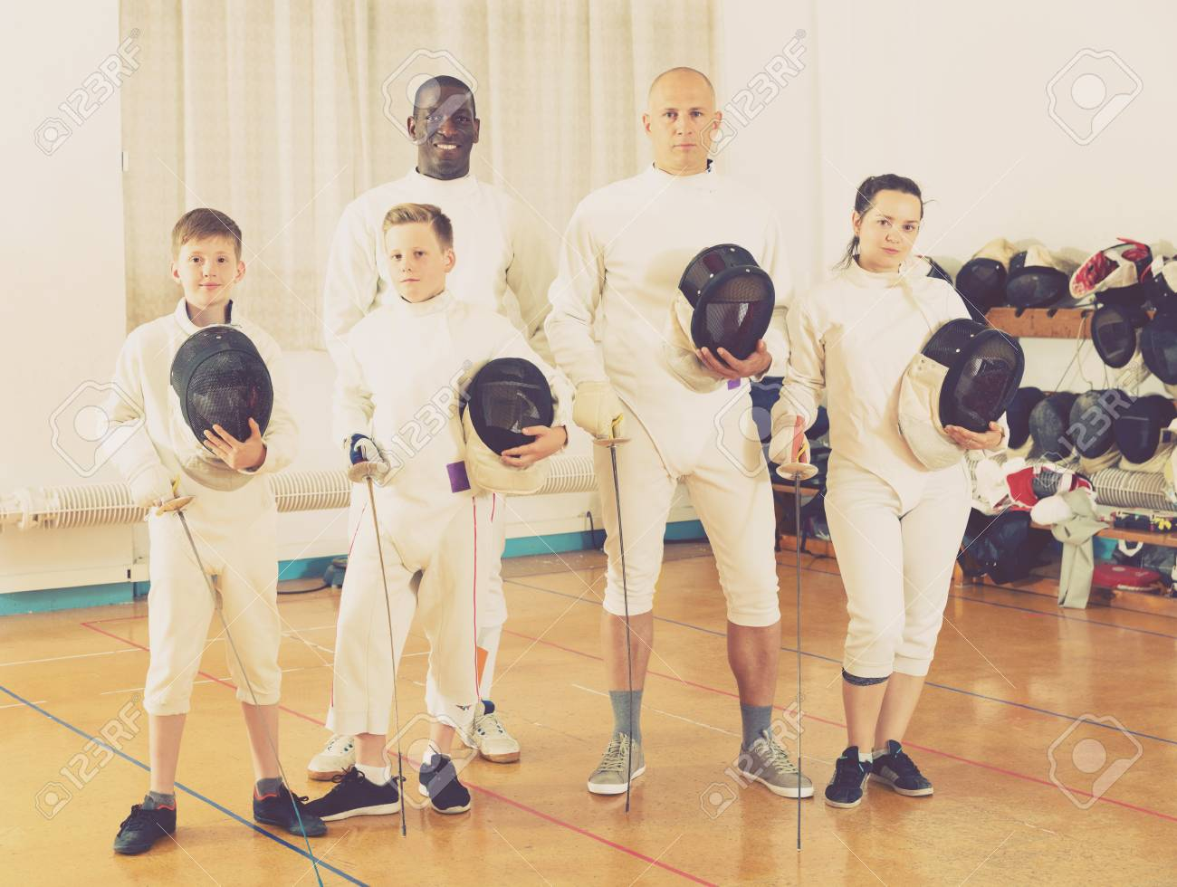 Portrait of happy adult and teen fencers in full fencing outfit