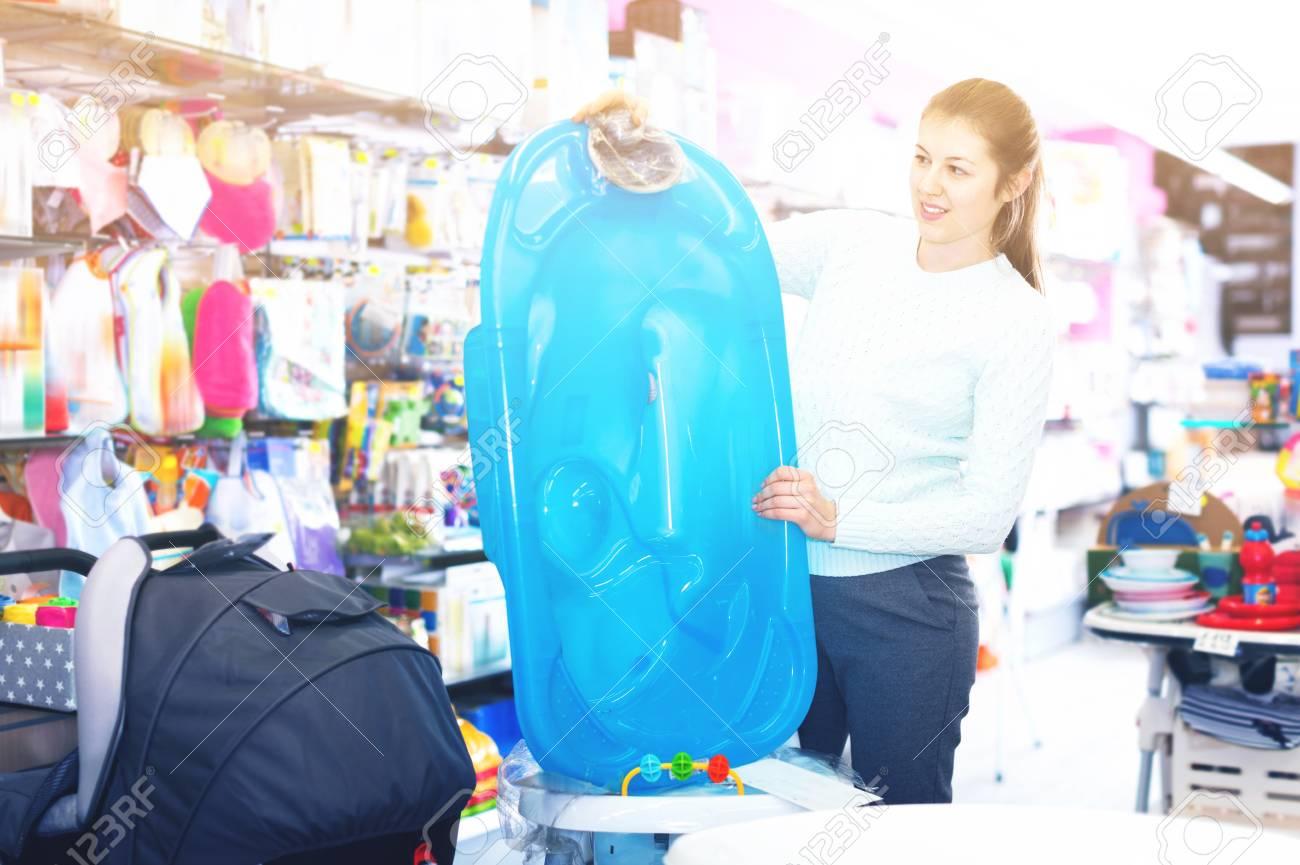 Happy Cheerful Pregnant Woman Is Choosing Baby Bath In The Shop ...