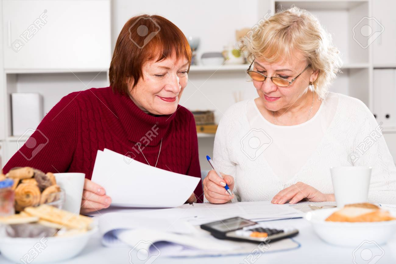 Stock Photo Two Positive Mature Women Considering Papers While Sitting On Kitchen