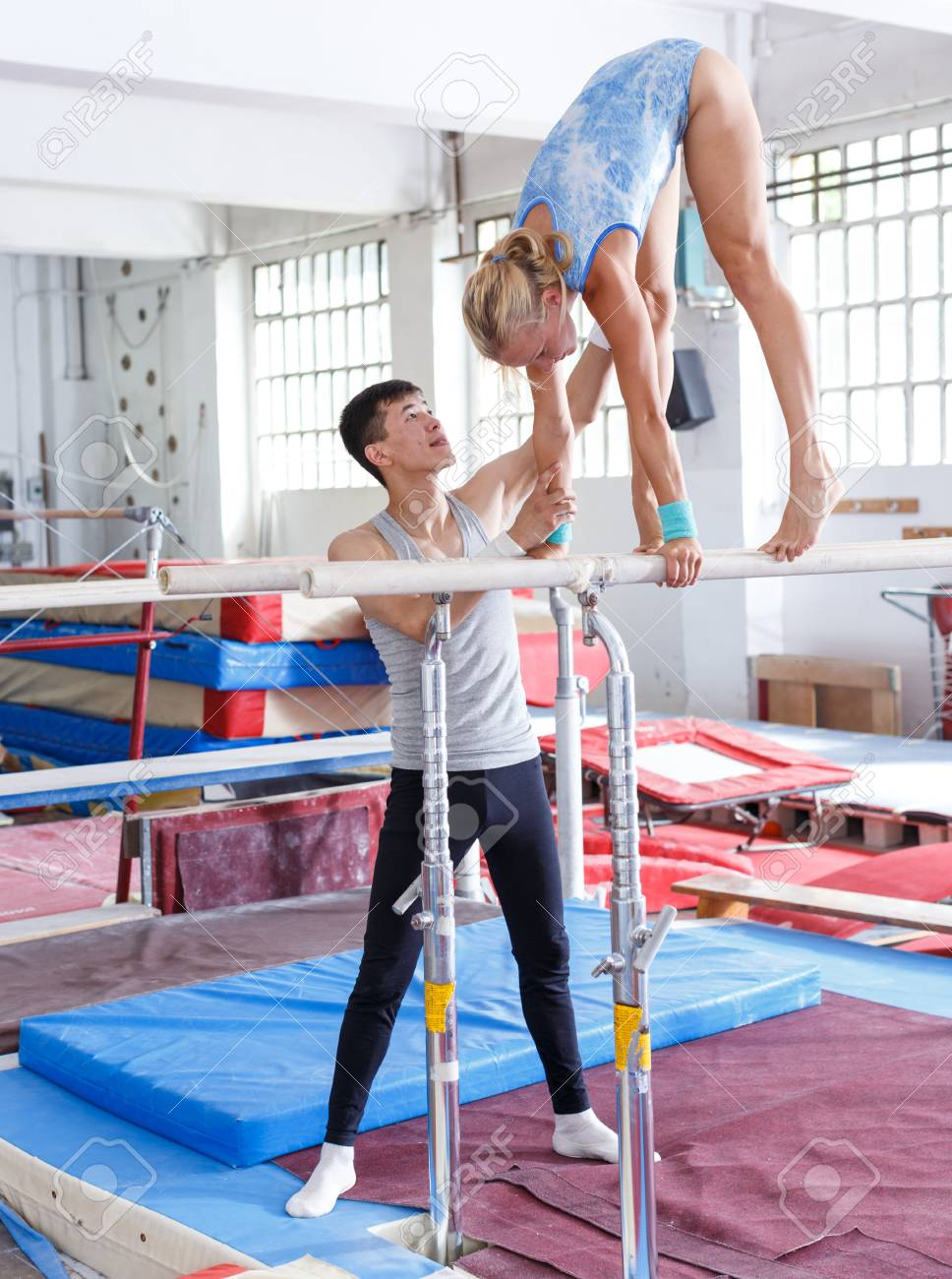 e59ececd61fc Athletic woman doing gymnastic exercises on parallel bars, man near  securing her Stock Photo -