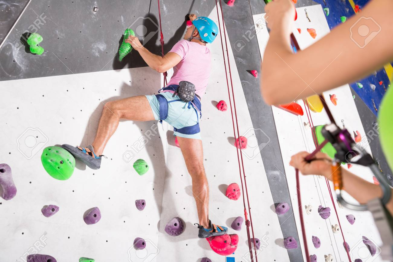 Sporty man dressed in rock climbing outfit training in bouldering gym - 106757811