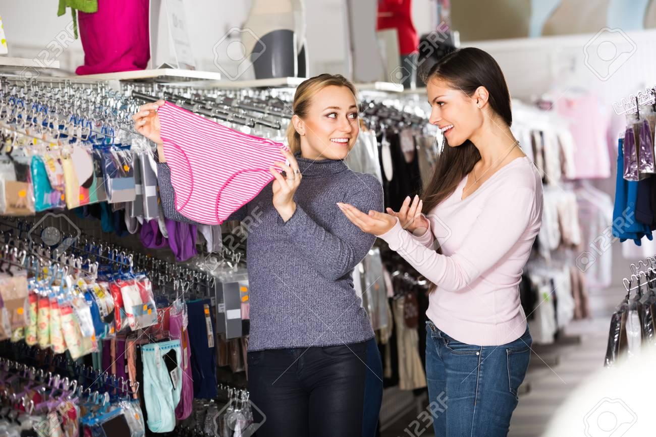 04cd78afebe8 Dos mujeres alegres que eligen cómodas bragas en la tienda de ropa interior