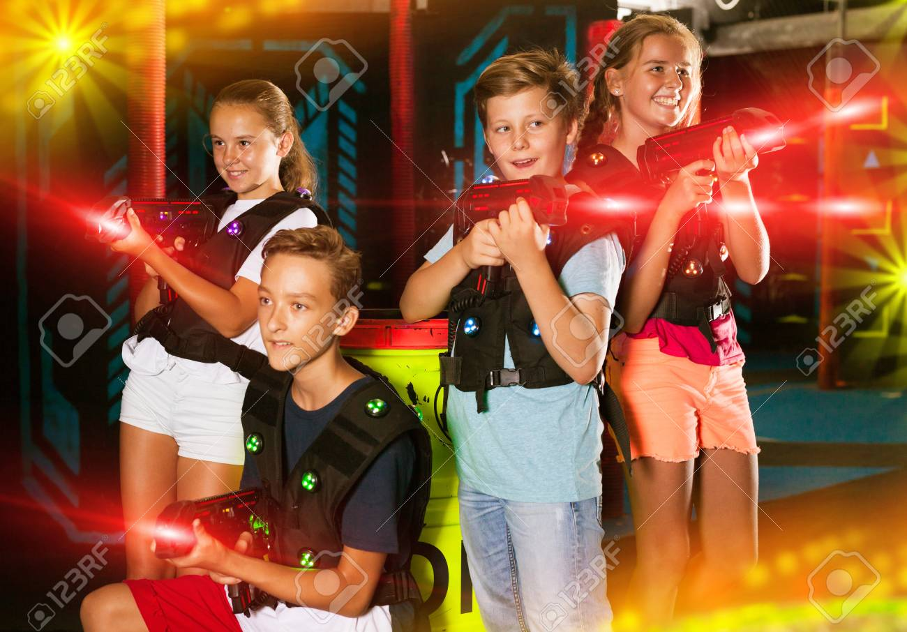 Cheerful teen girls and boys with laser pistols posing together..