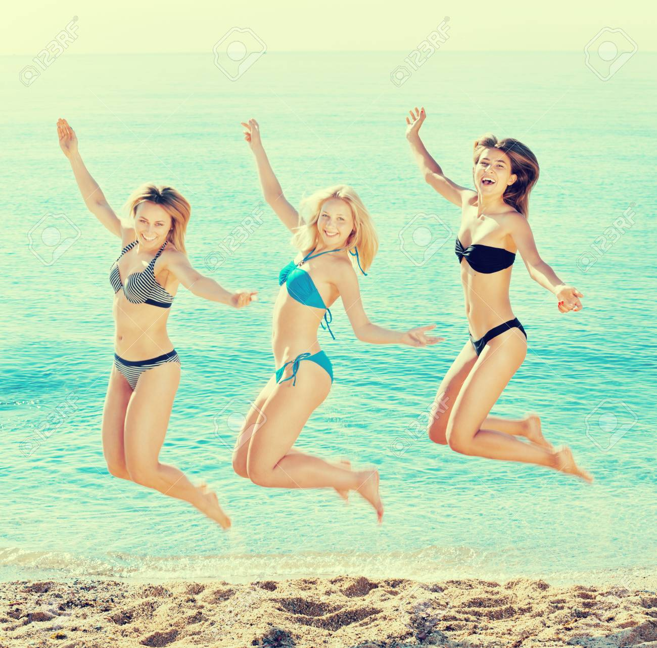 465a884ecf1 Portrait of three cheerful young women in swimsuits hopping together..