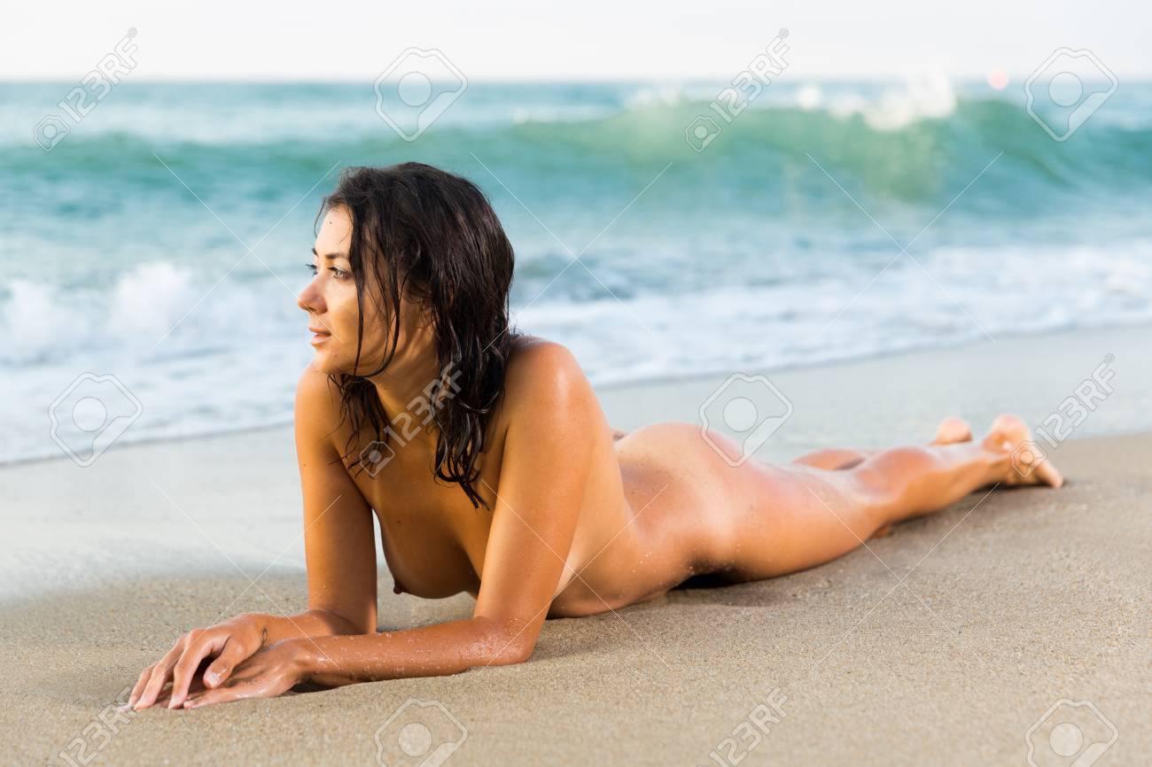 Nude Girl Lying On Stomach In Graceful Pose On Sand Beach Against