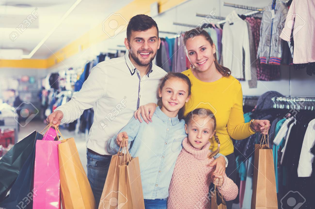 0f91727f4 Young smiling family with two daughters after shopping in clothes store  Stock Photo - 110627062