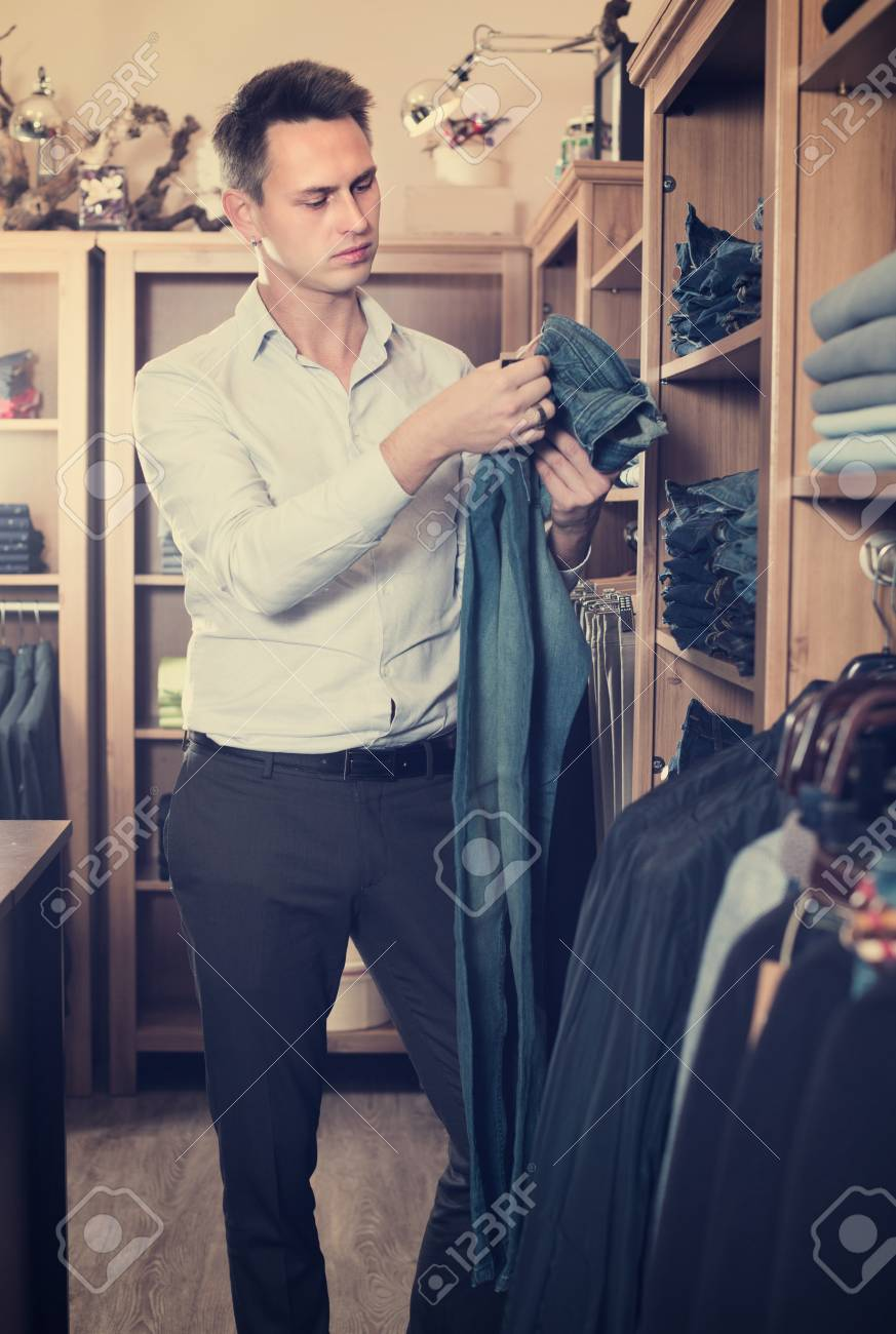 2d55a985 Young man is choosing on new pants in men's clothes store. Stock Photo -  111064512