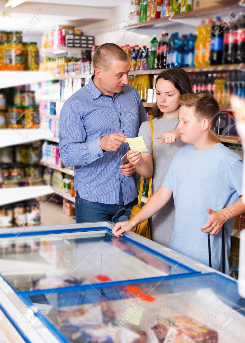 positive young family with tween boy making purchases together