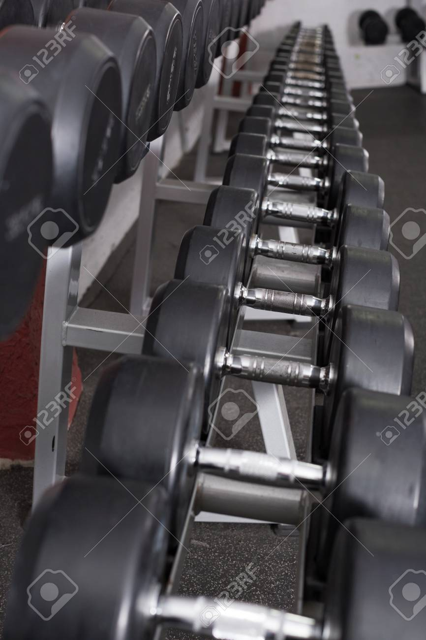 Rows of dumbbells for weight training in gym - 113140580