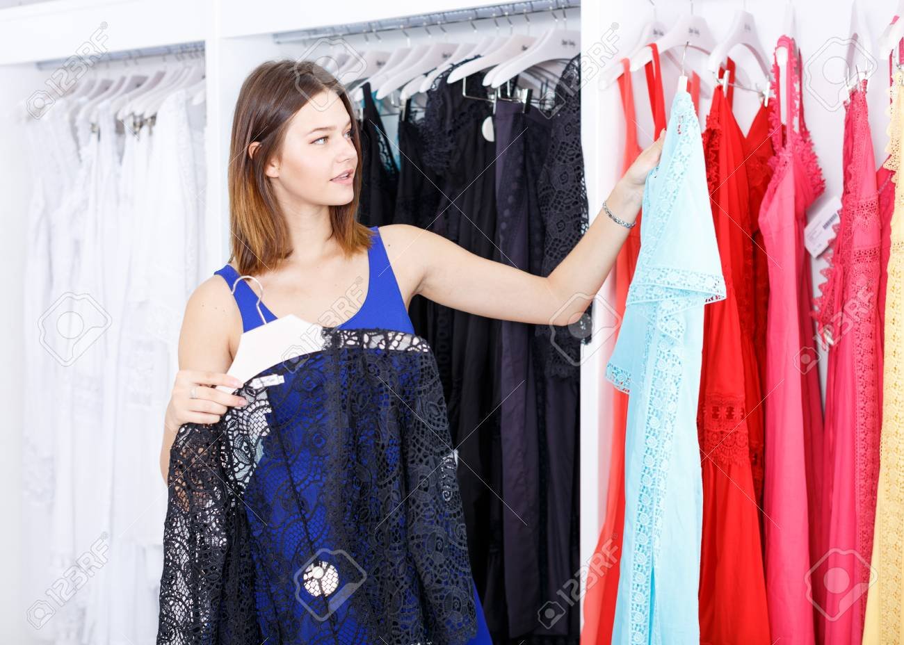 60092ca055 Young cheerful woman shopping in clothing boutique Stock Photo - 113777464