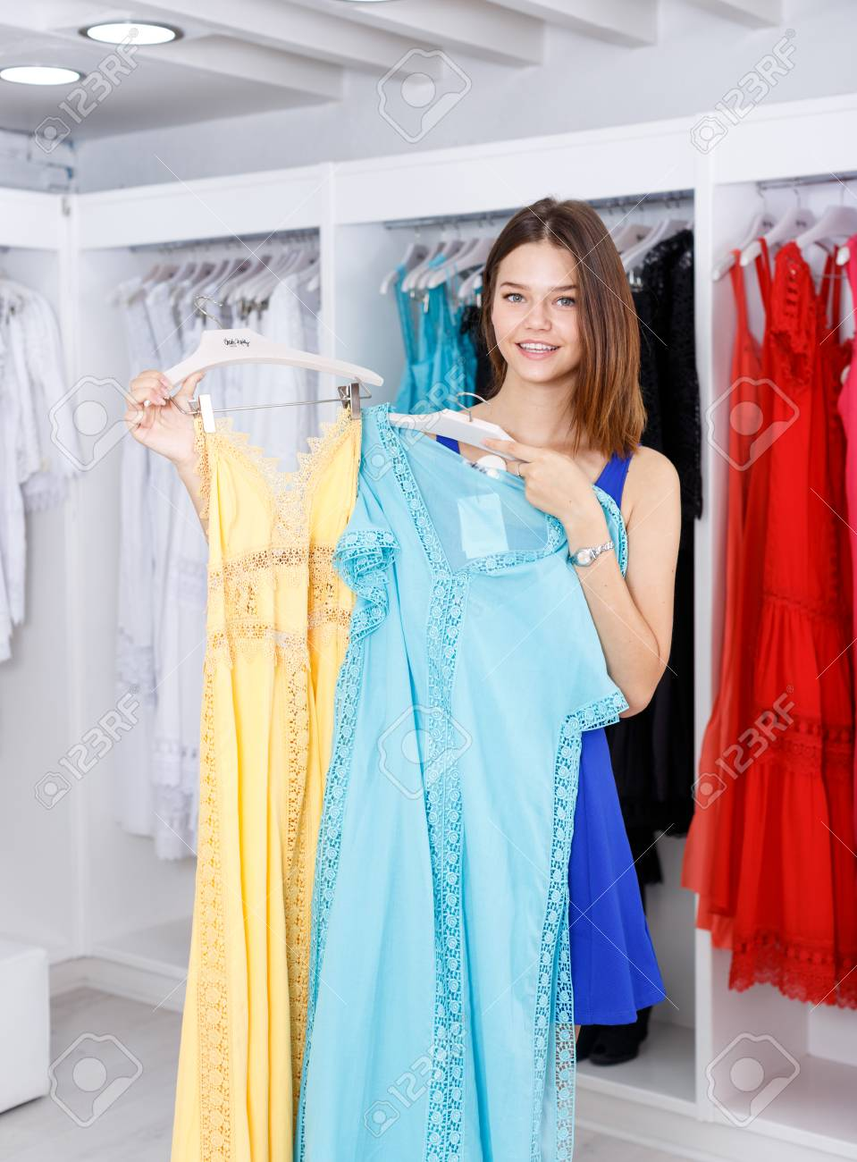 ccec63a7f3 Young cheerful woman shopping in clothing boutique Stock Photo - 113777783