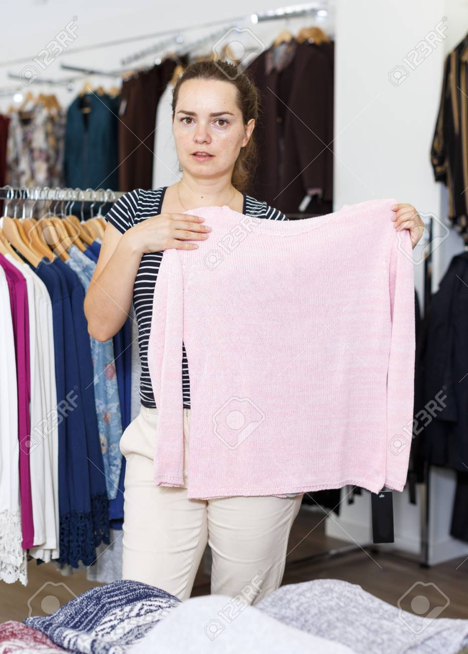440c324a2d Young cheerful woman shopping in clothing boutique Stock Photo - 113843665