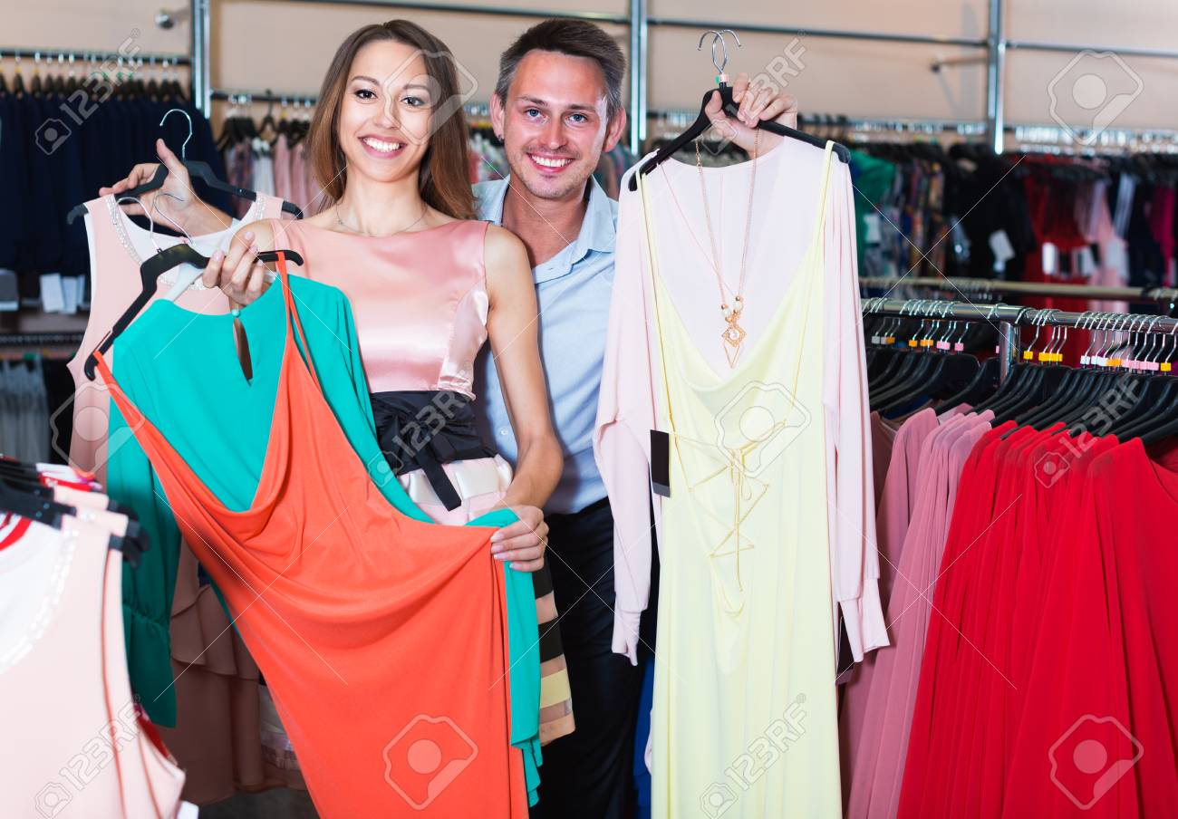 1fafcba3ab Family couple is demonstrating dresses that they chose in women clothes shop.  Stock Photo -