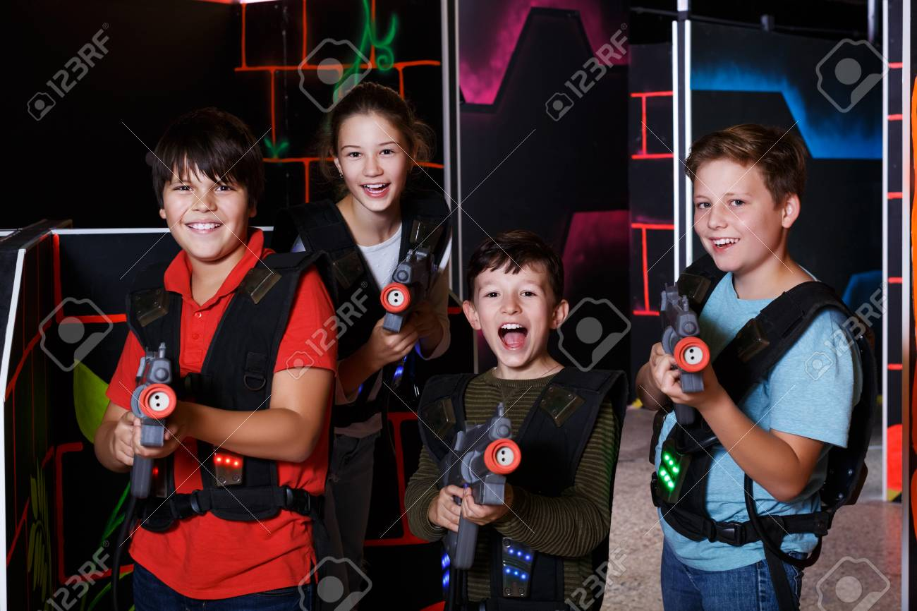 Portrait of happy excited teen kids with laser guns during lasertag
