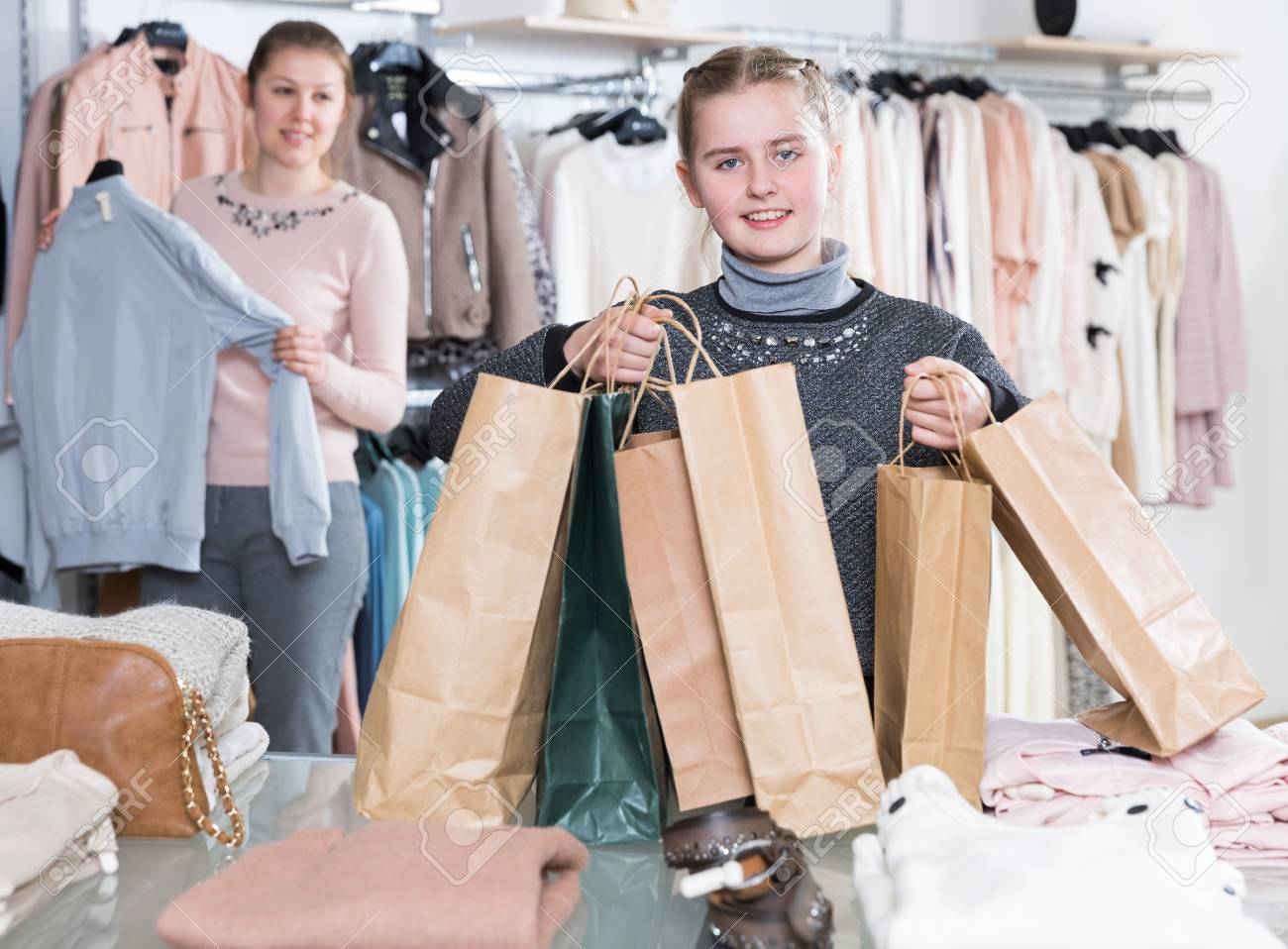f092046ae Happy girl holding many bags after family shopping with mother in modern clothing  store Stock Photo