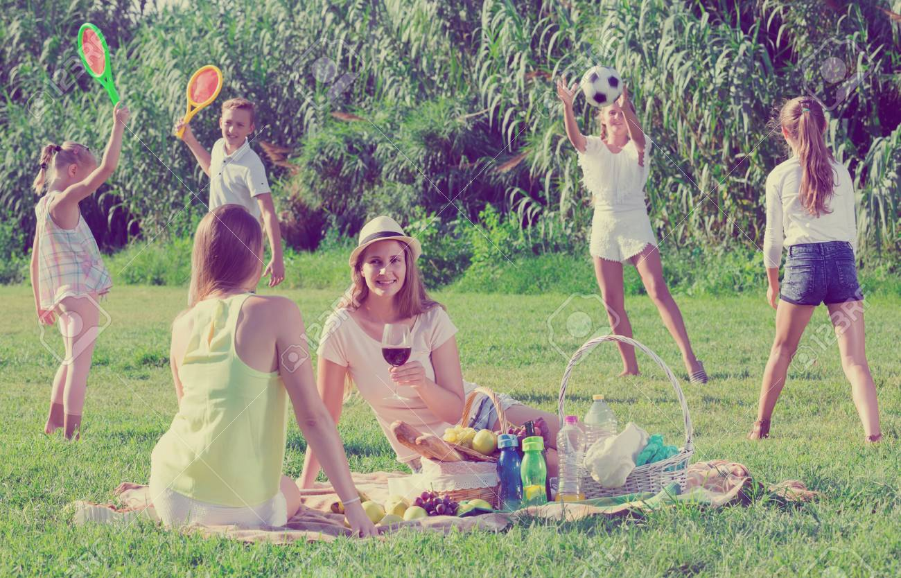 Cheerful british females on picnic outdoors on background with