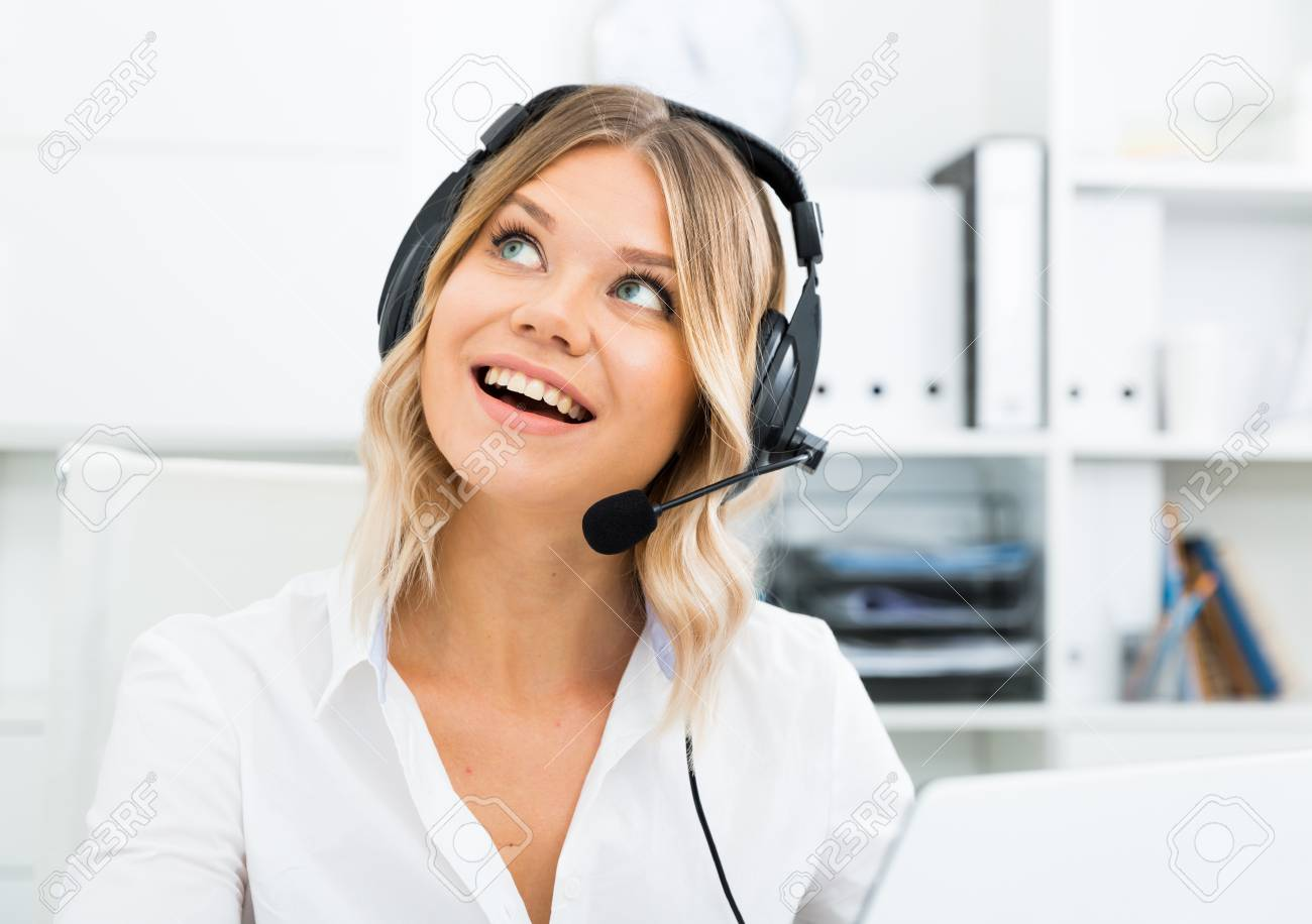 Young girl in call center with headphones sitting with laptop - 120553414