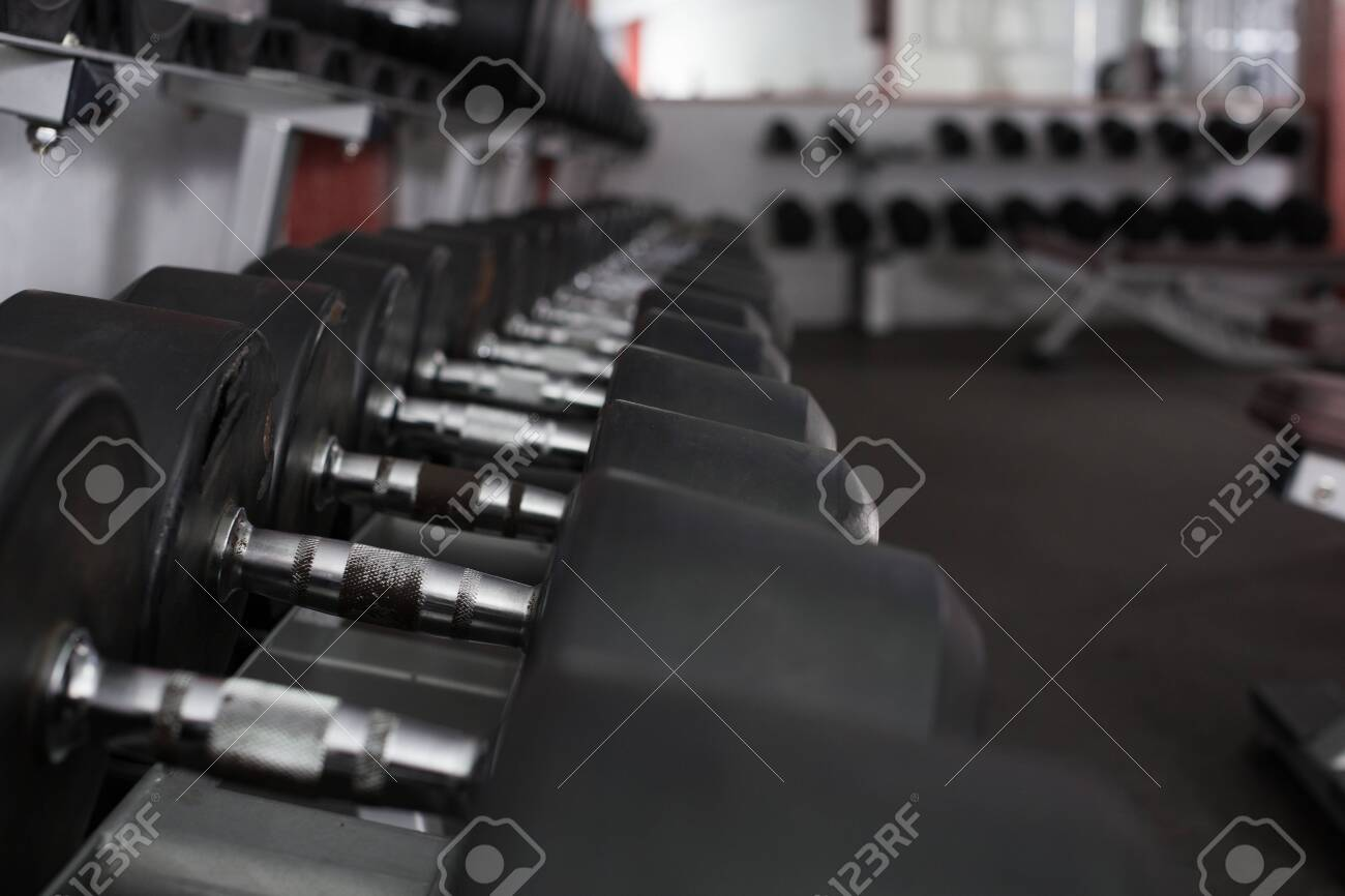 Rows of dumbbells for weight training in gym - 120952254