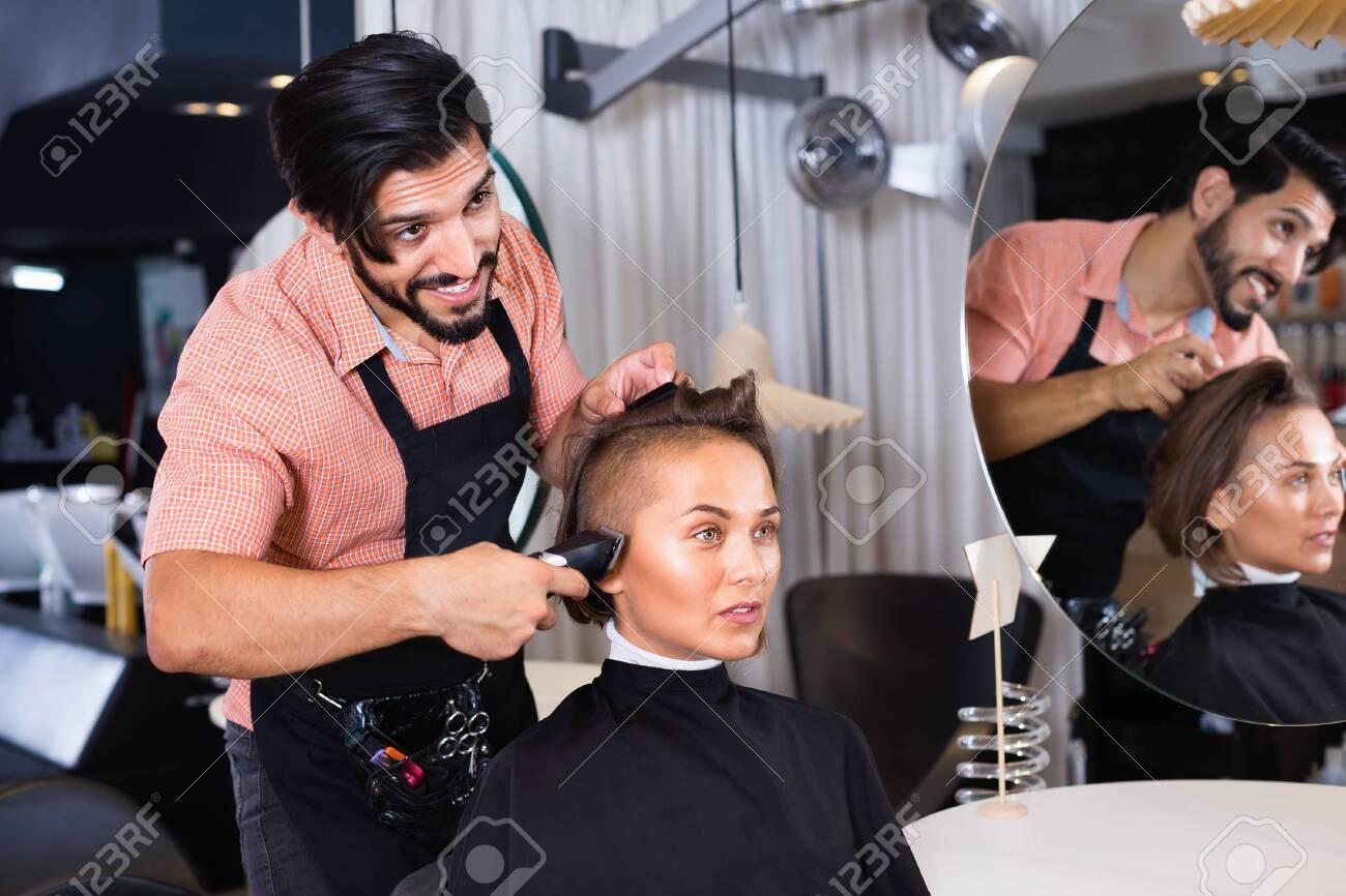 Portrait of cheerful positive man hairdresser cutting woman's hair in salon - 120935273